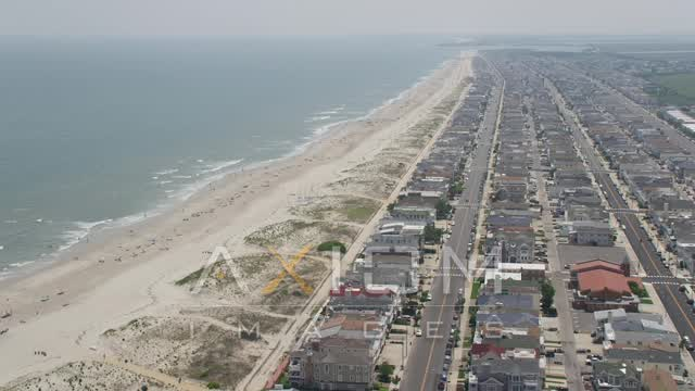Sunbathers and oceanfront homes in Ocean City, New Jersey Aerial Stock Footage | AX71_230