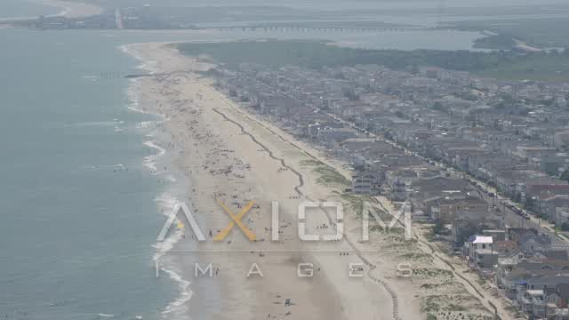 Sunbathers and oceanfront property in Ocean City, New Jersey Aerial Stock Footage | AX71_231