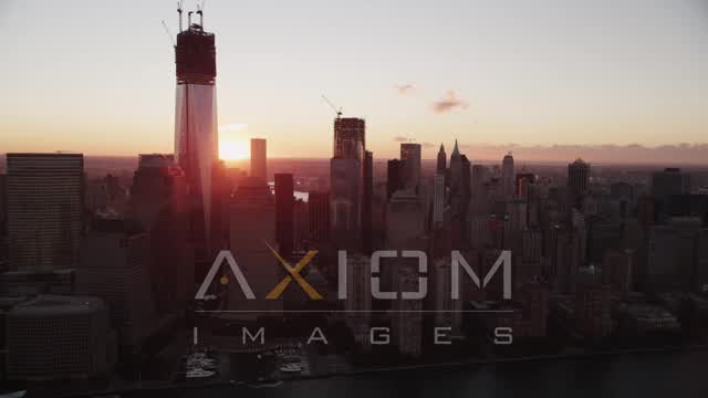 Flying by Lower Manhattan skyscrapers, New York, New York, sunrise Aerial Stock Footage | AX90_009