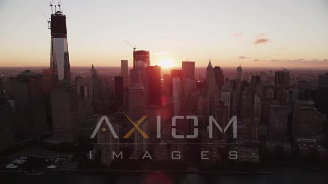 Flying by Lower Manhattan skyscrapers, New York, New York, sunrise Aerial Stock Footage | AX90_010