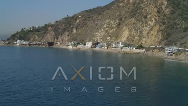 Flying over the ocean, approaching coastal Malibu homes, Malibu, California Aerial Stock Footage | DCA05_104