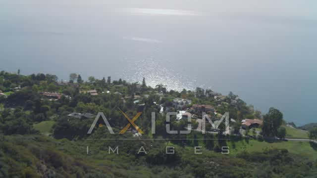 Hiking trail on hill, homes on cliff overlooking the Pacific Ocean, Malibu, California Aerial Stock Footage | DCA05_110