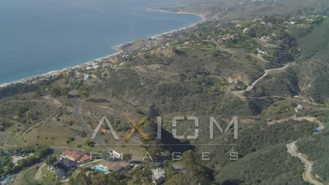 Pan across hills, revealing residential neighborhoods, coastline, Malibu, California Aerial Stock Footage | DCA05_111