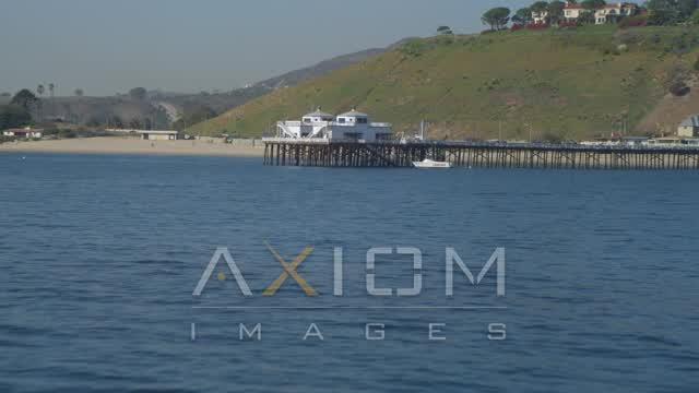 Flying over small waves in ocean, revealing Malibu Pier, Malibu, California Aerial Stock Footage | DCA05_119