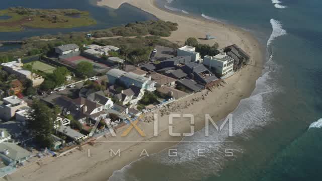 Pan from Malibu Lagoon to coastal homes, tilt up, flying away, Malibu, California Aerial Stock Footage | DCA05_121