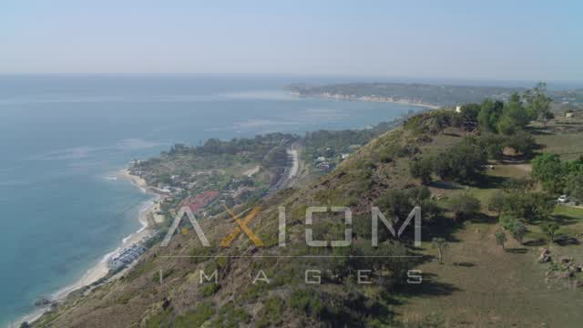 Flying over a hill, revealing Pacific Ocean, Malibu, California Aerial Stock Footage | DCA05_125