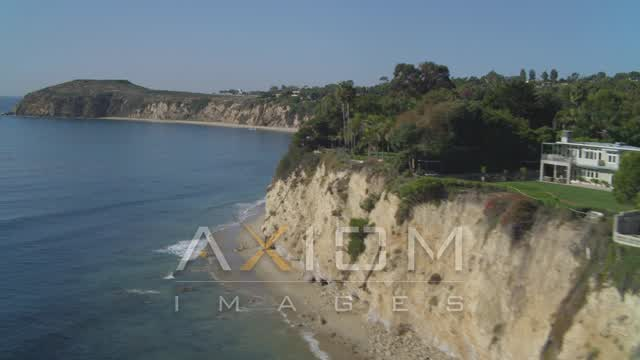Fly low over ocean, ascend near coastal mansion, Dume Cove, Malibu, California Aerial Stock Footage DCA05_130