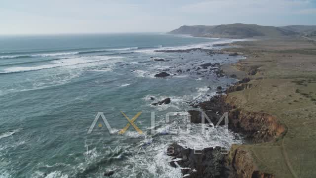 Fly over coastal cliffs and empty beach, and tilt up to follow the coast, Estero Bay, California Aerial Stock Footage DCSF03_004