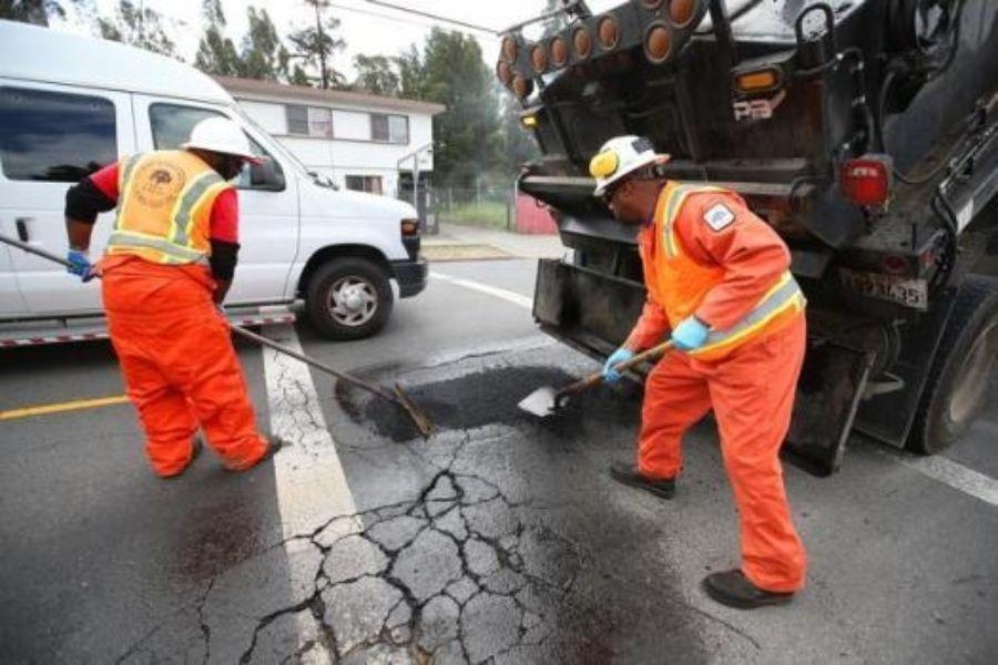 crew fixes pothole