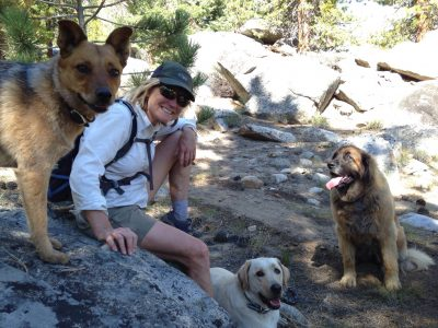 photo of woman hiker with three dogs