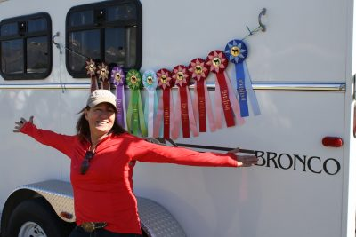 image of a woman standing in front of a line of show ribbons
