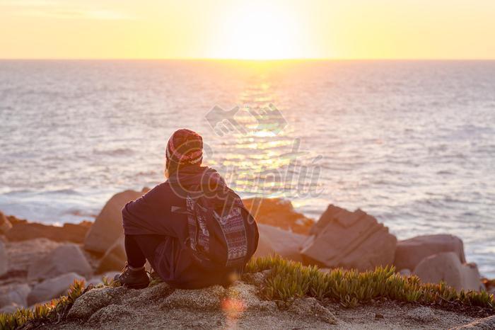 Mujer sentada en las rocas observando el atardecer en el mar