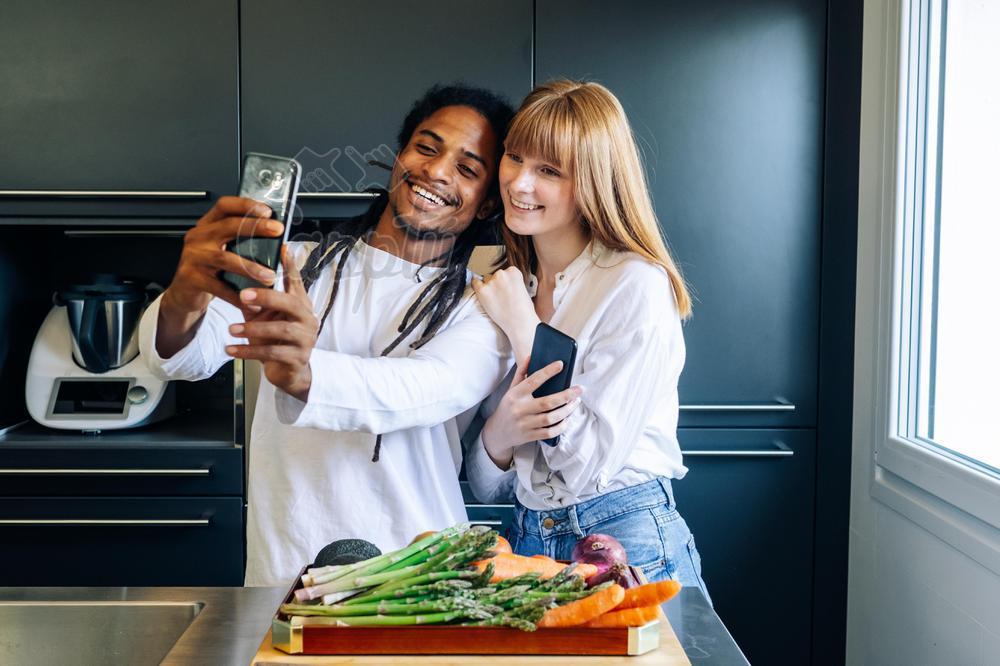 chico afro y chica blanca haciendose un selfie en la cocina