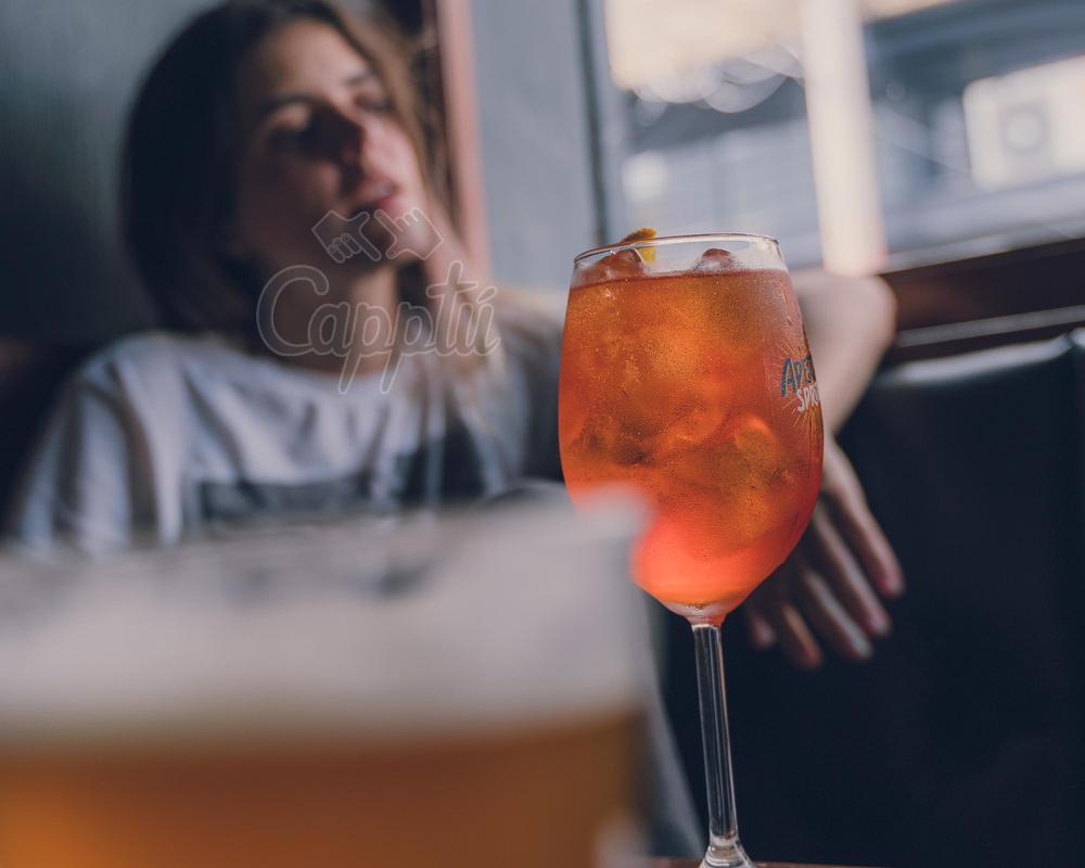 Mujer con copa en un bar con luz de día