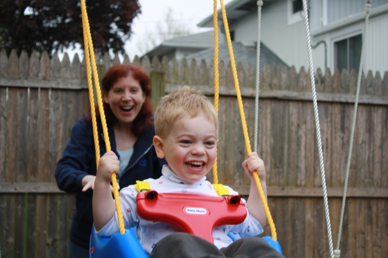 On our backyard swing set with Grandma Risa.