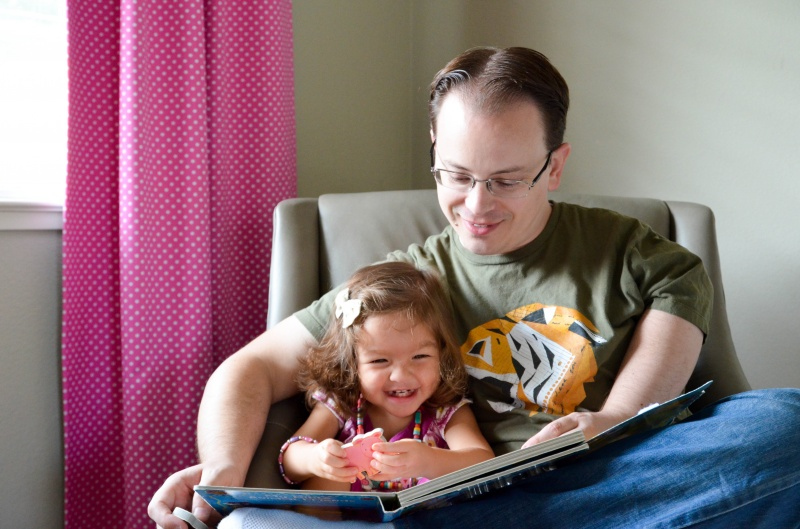 Chris reading a book with our friend's daughter, Zoey