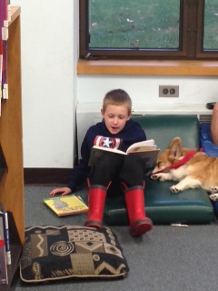 Brandon loves reading to the dogs at the library.