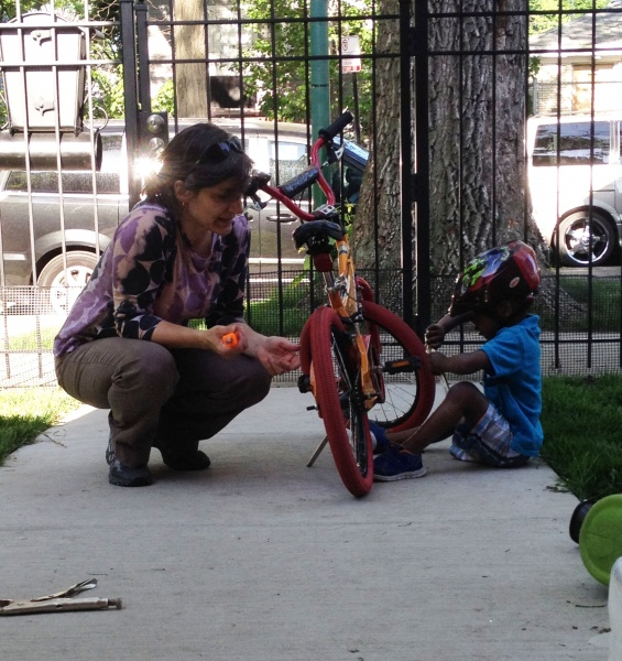 Shaila helping a little visitor with his bike.