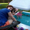 At our summer party, Kristia helps with the kids by the pool.