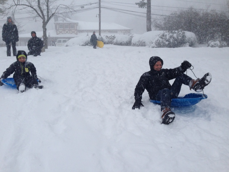 Guillaume riding on a sled with our neighbors during the big snowstorm last year