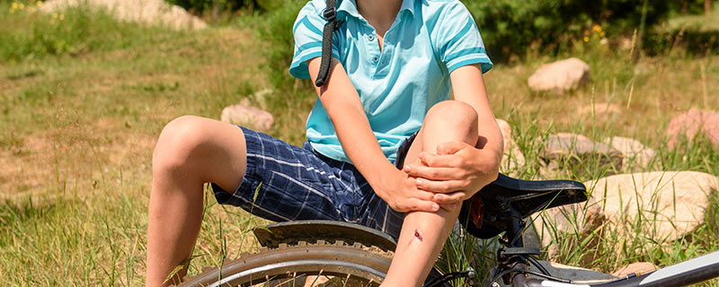 kid-with-knee-pain-on-bike