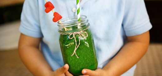Spinach green smoothie holding by a child as healthy summer drink