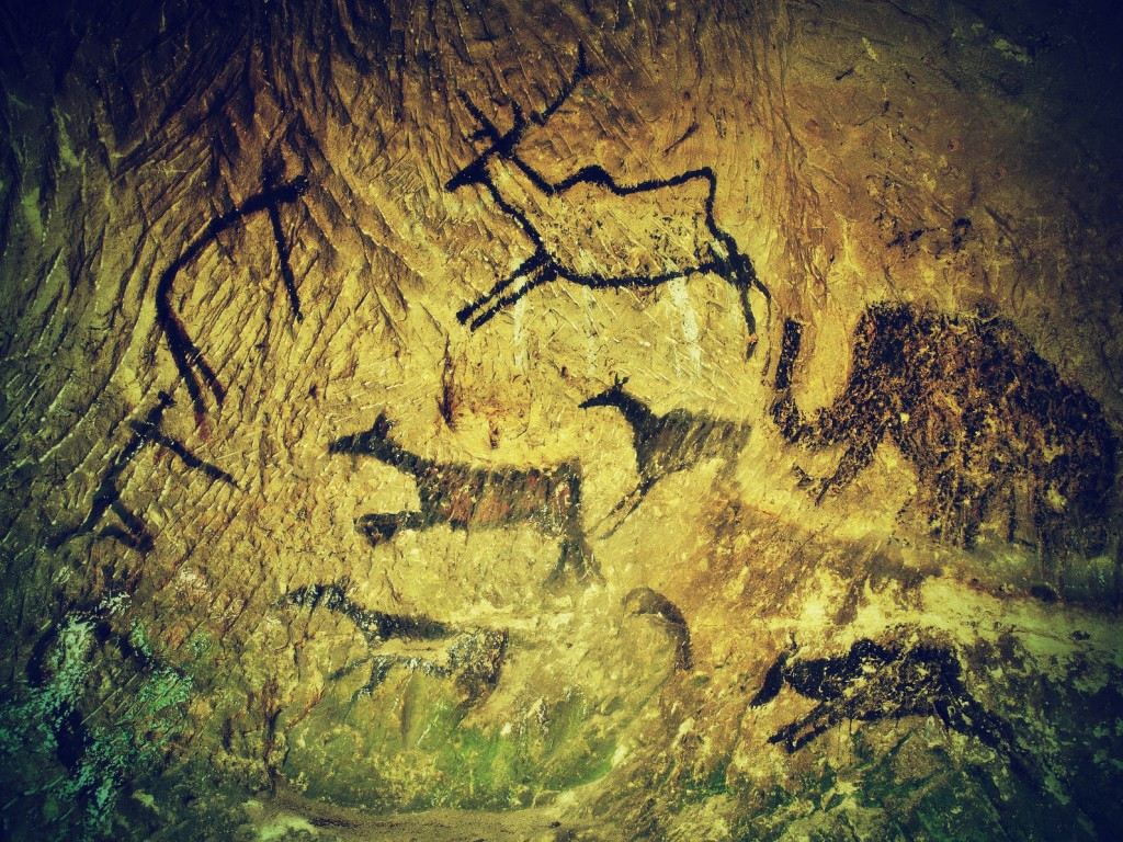 Abstract children art in sandstone cave. Black carbon paint of human hunting on sandstone wall, copy of prehistoric picture.