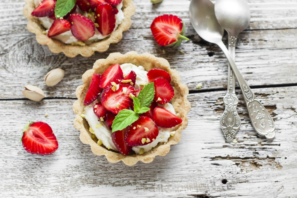 tartlets with cream cheese and strawberries on a light wooden background
