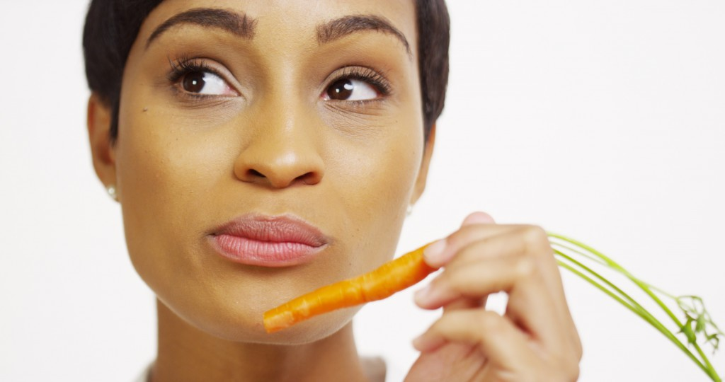 Close up of African woman eating carrot and smiling