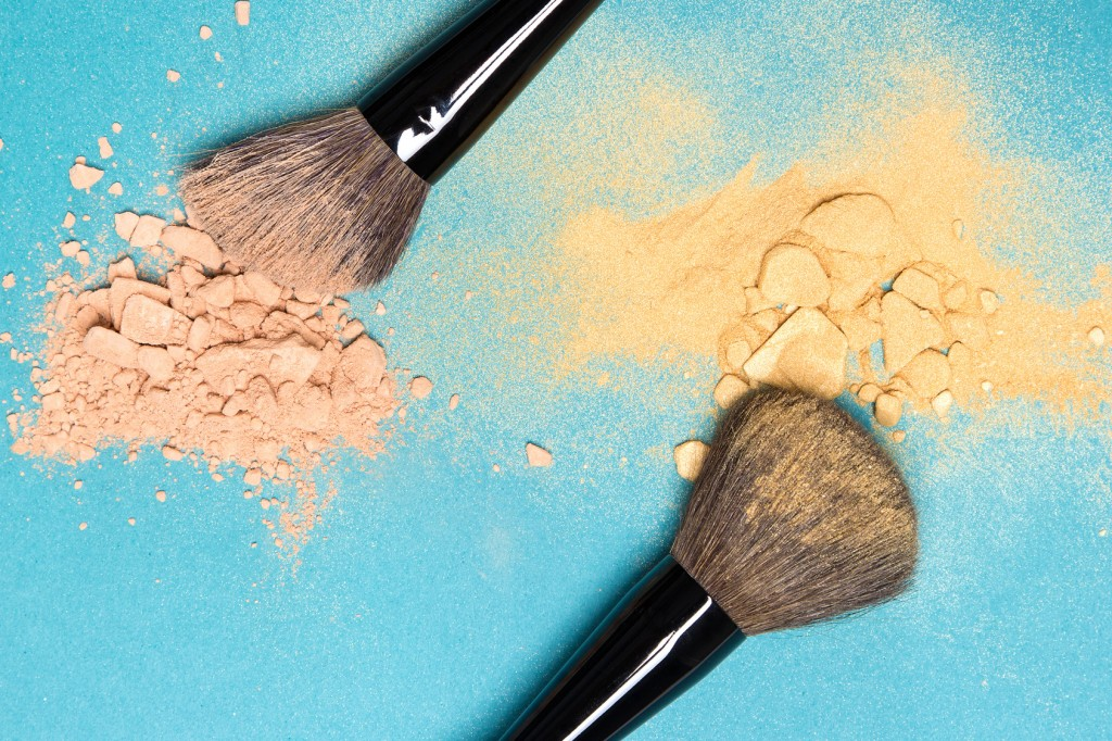 Close-up of crushed mineral matte compact powder and shimmer powder golden color with makeup brushes on blue background