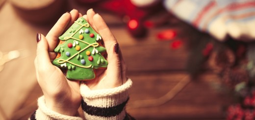 Woman wrapping a christmas cookie on wooden background, photo from high point of view