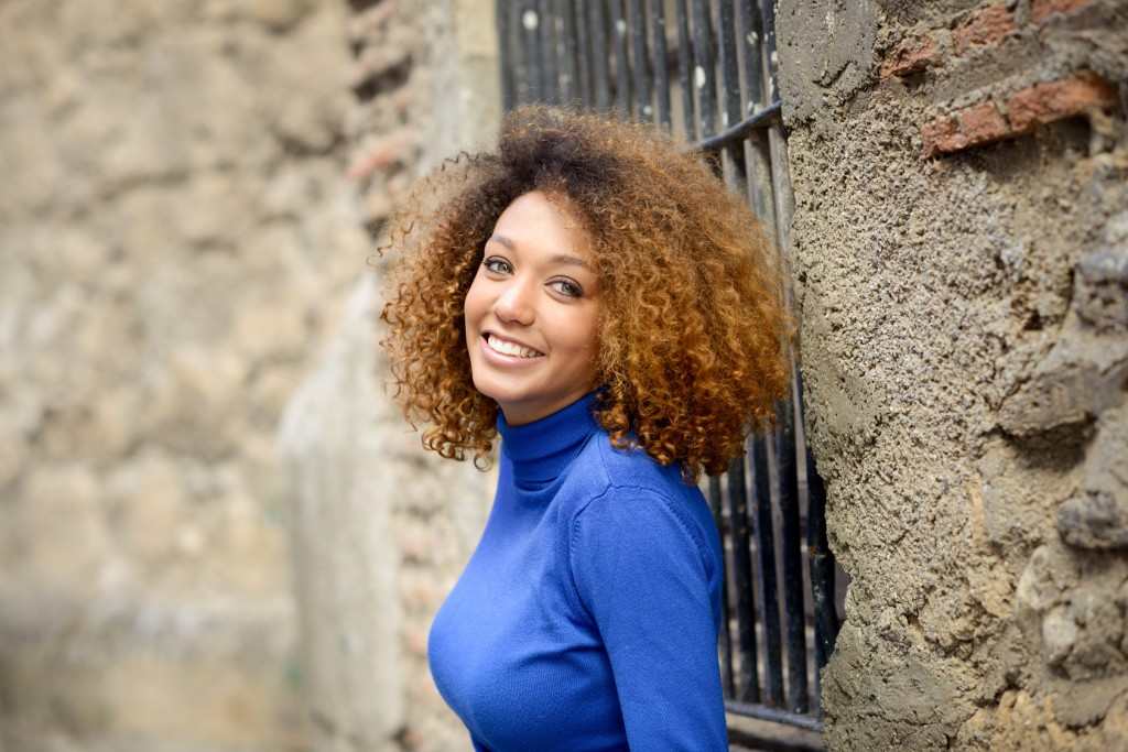 Beautiful young African American woman, model of fashion, smiling with afro hairstyle and green eyes wearing blue sweater in urban background