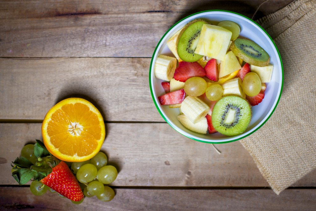 Fresh fruit salad in bowl on wooden background.