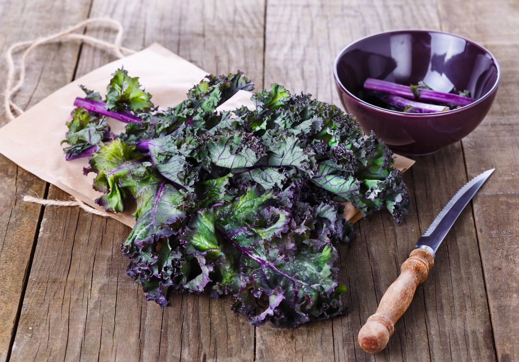 Bunch of organic kale in a woven basket on a rustic wooden background. Selective focus, shallow dof
