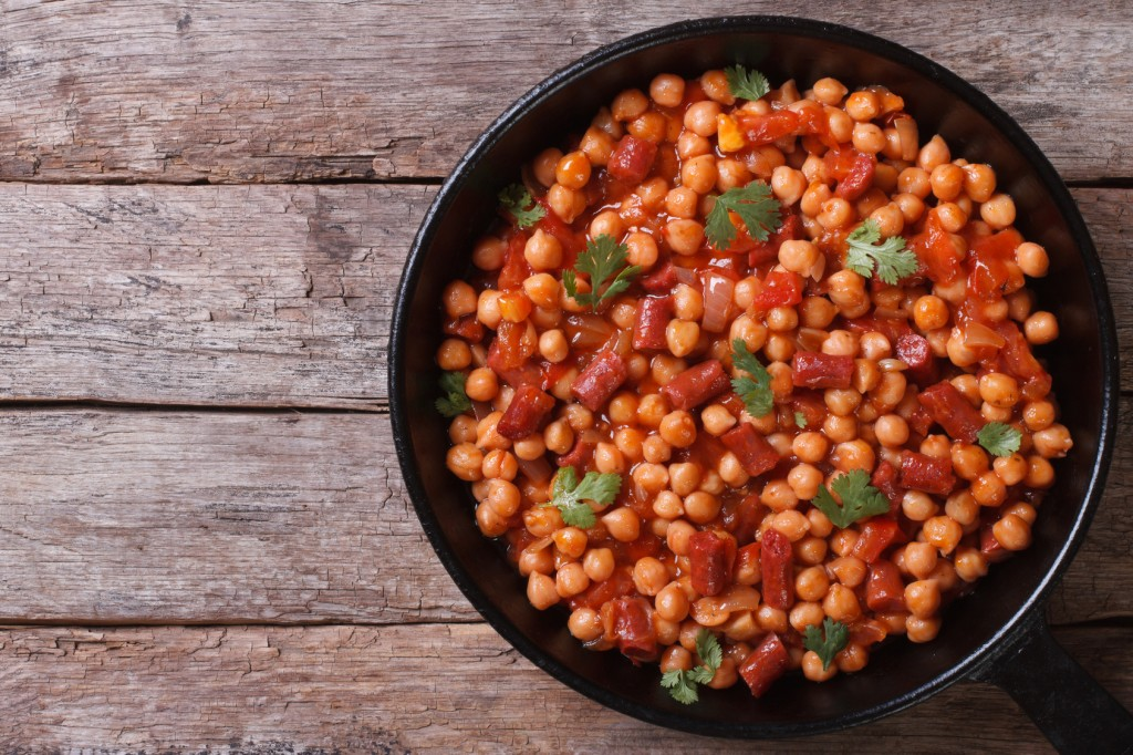 Chickpeas with chorizo in a pan top view