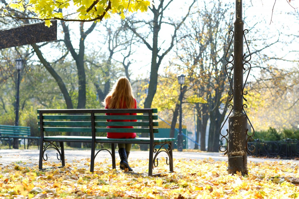 Lonely woman on bench in park