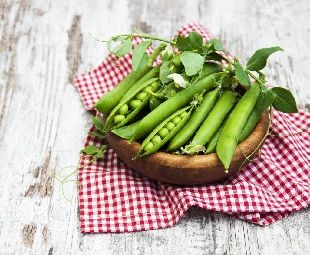 Bowl with fresh peas on a old wooden background