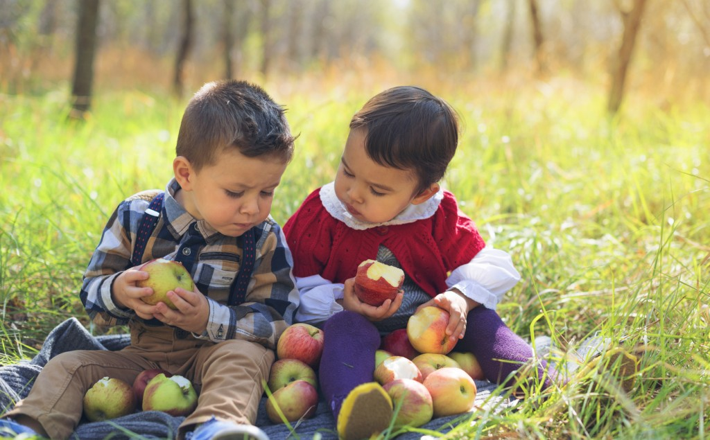 two little kids eating apples in the park