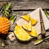 Sliced fresh pineapple with a knife on a chopping Board. On wooden background.  Top view