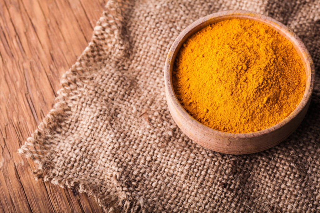 dry turmeric in a wooden bowl close-up on a vintage background