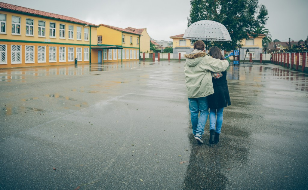 Back view of young couple embracing under the umbrella walking in an autumn rainy day. Love and couple relationships concept.