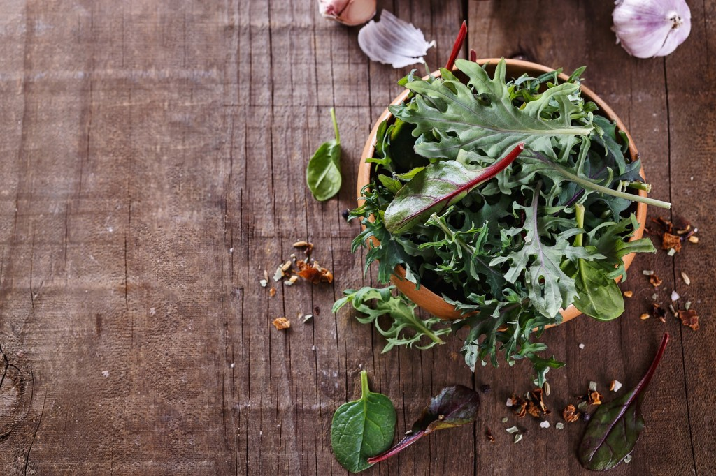 Leafy green mix of kale, spinach, baby beetroot leaves over rustic wooden background. Copy space, selective focus
