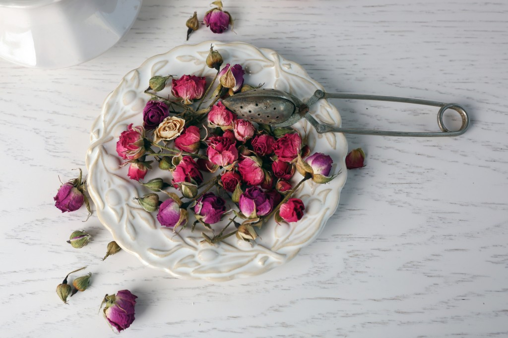 Tea rose flowers on plate on wooden table