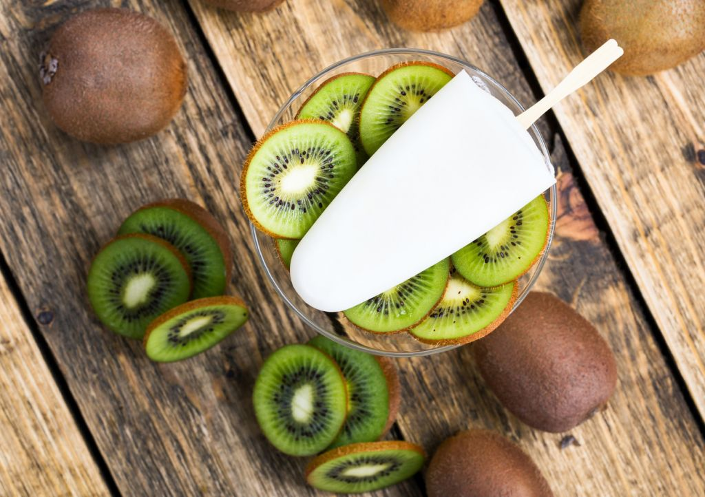 Homemade ice cream with fresh kiwi and frozen yogurt on wooden table, top view