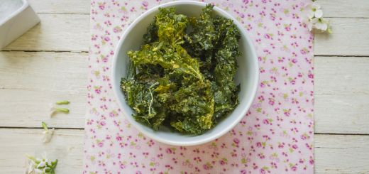 Delicious kale chips on white bowl and pink flowered napkin, ready to enjoy a gourmet snack.