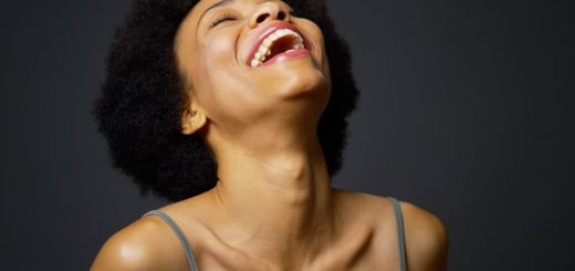 Slow pan up casual black woman laughing and smiling