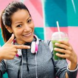 Successful fitness urban woman taking a rest for drinking and recommending detox smoothie. Healthy nutrition and lifestyle concept.