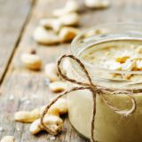 toasted cashew coconut butter on a dark wood background. toning. selective focus