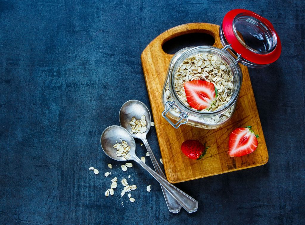Oat flakes in gar with fresh strawberries for breakfast on dark vintage background with space for text. Healthy food, Diet, Detox, Clean Eating or Vegetarian concept.