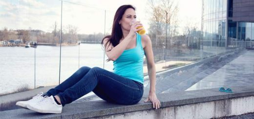 woman-drinking-juice-on-bench